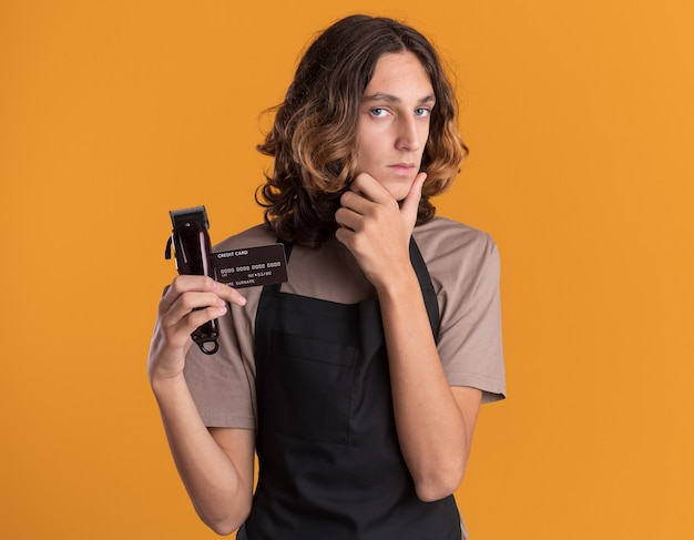 自信を持って若いハンサムな床屋は、クレジットカードとバリカンを持って制服を着て、あごに手を置いています