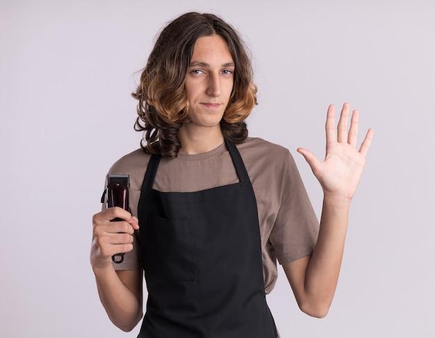 白い壁に隔離された手で5を示す正面を見てバリカンを保持している制服を着ている自信を持って若いハンサムな床屋