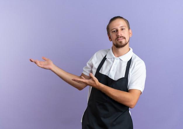 紫色で隔離された側で手を指している制服を着ている自信を持って若いハンサムな理髪師