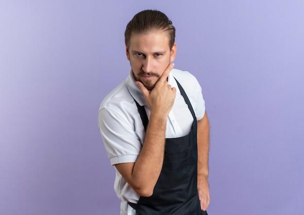 自信を持って若いハンサムな理髪師は、あごに手を置き、コピースペースで紫色に分離された腰にもう1つを着て制服を着ています