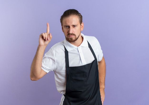 自信を持って若いハンサムな理髪師は、腰に手を置き、コピースペースで紫色に分離された上向きの制服を着ています