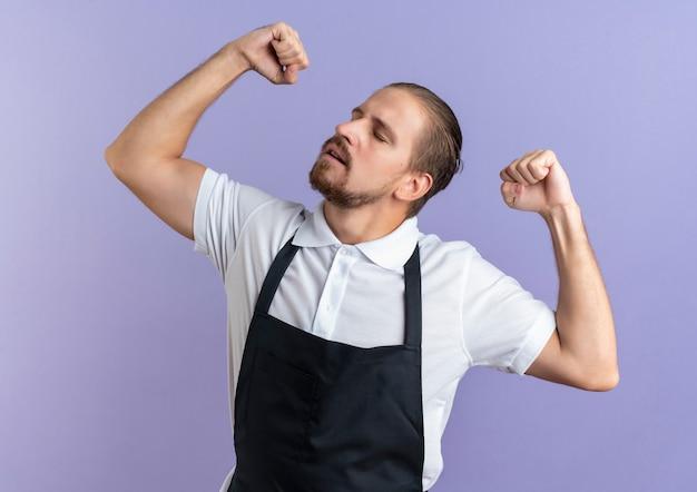 紫色で隔離された目を閉じて強く身振りで示す制服を上げている拳を身に着けている自信を持って若いハンサムな理髪師