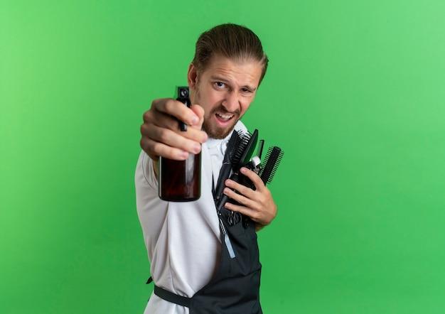 Уверенный молодой красивый парикмахер в униформе, стоящий в профиле, держа расчески, машинки для стрижки волос и протягивая распылитель к камере, изолированной на зеленом фоне с копией пространства