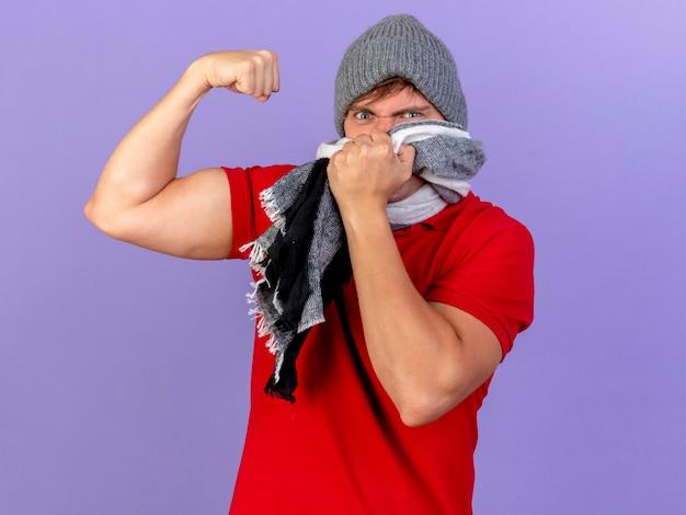 冬の帽子とスカーフを身に着けている自信を持って若いハンサムな金髪の病気の男は、コピースペースで紫色の壁に隔離された強いジェスチャーを口にスカーフを維持します