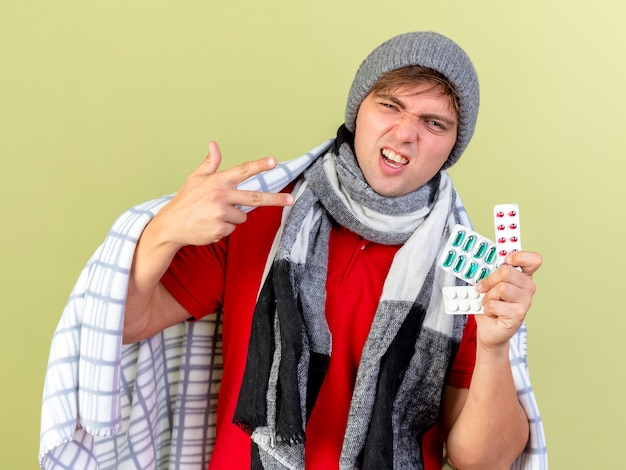 Confident young handsome blonde ill man wearing winter hat and scarf wrapped in plaid holding packs of medical pills looking at camera isolated on olive green background