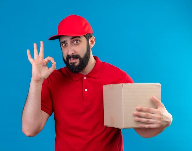 Уверенный молодой красивый кавказский курьер в красной форме и кепке держит картонную коробку и делает знак ок, изолированный на синем