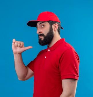 Уверенный молодой красивый кавказский курьер в красной форме и кепке, стоящий в профиле, указывая на себя, изолированного на синем