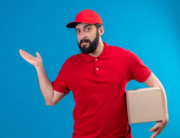 Fiducioso giovane uomo di consegna caucasico bello che indossa uniforme rossa e cappuccio che tiene la scatola di cartone e mostrando la mano vuota isolata sull'azzurro