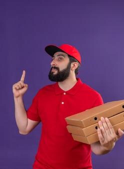 Fiducioso giovane uomo di consegna caucasico bello che indossa l'uniforme rossa e il cappuccio che tiene le scatole per pizza guardando il lato e rivolto verso l'alto isolato sulla porpora