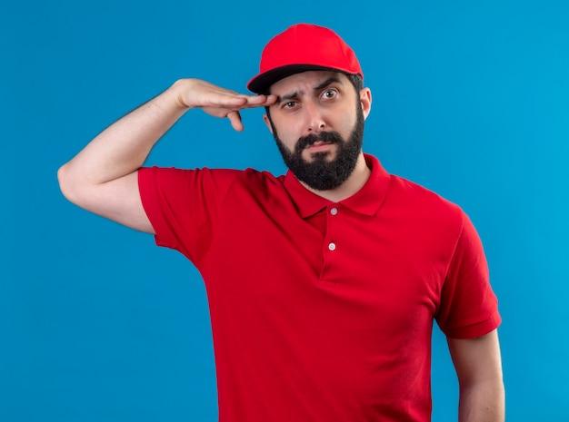 Fiducioso giovane uomo di consegna caucasico bello che indossa l'uniforme rossa e cappuccio mettendo la mano vicino alla testa isolata sull'azzurro