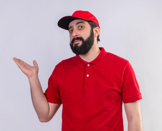 Fiducioso giovane uomo di consegna caucasico bello che indossa l'uniforme rossa e cappuccio che mostra la mano vuota isolata su bianco
