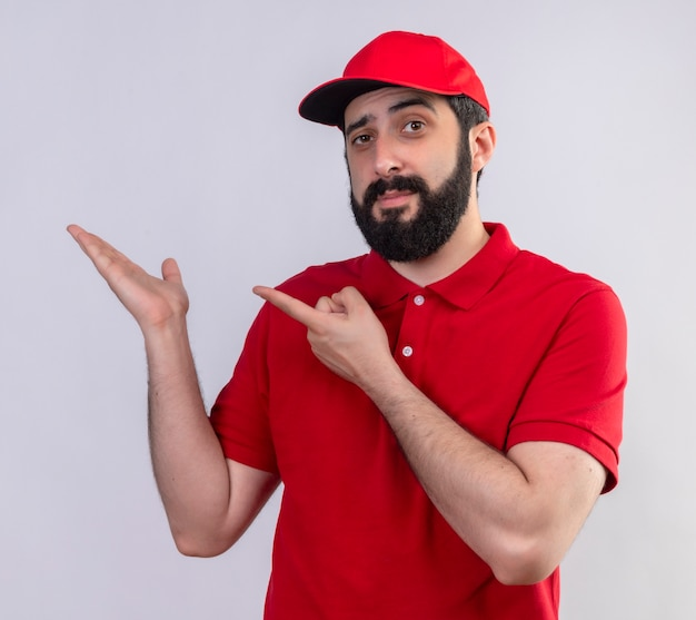 Confident young handsome caucasian delivery man wearing red uniform and cap showing empty hand and pointing at it isolated on white