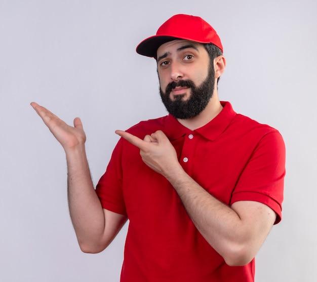 Fiducioso giovane uomo di consegna caucasico bello che indossa l'uniforme rossa e cappuccio che mostra la mano vuota e che punta a esso isolato su bianco