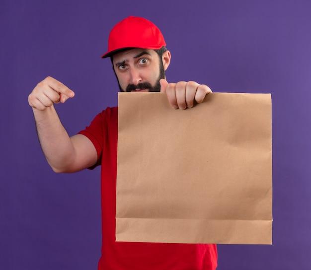 Fiducioso giovane uomo di consegna caucasico bello che indossa l'uniforme rossa e il cappuccio che allunga il pacchetto di carta verso la telecamera e che punta a esso isolato sulla porpora