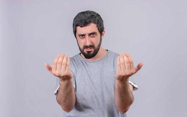 Fiducioso giovane uomo caucasico bello che fa venire qui gesto isolato su bianco con lo spazio della copia