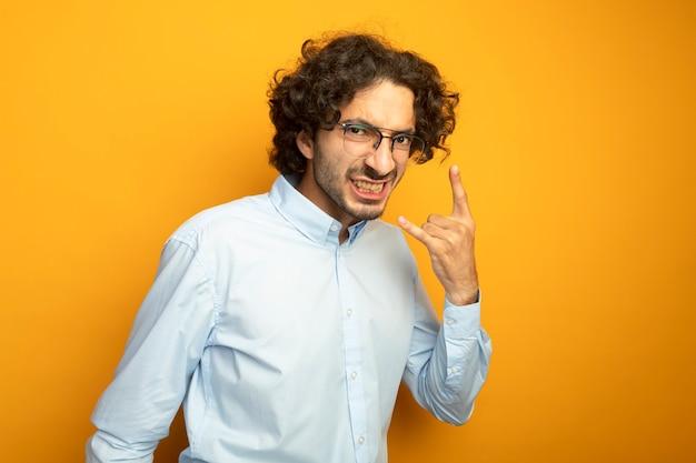 Уверенный молодой красивый кавказский мужчина в очках смотрит в камеру, показывая зубы, делая рок-знак, изолированный на оранжевом фоне с копией пространства