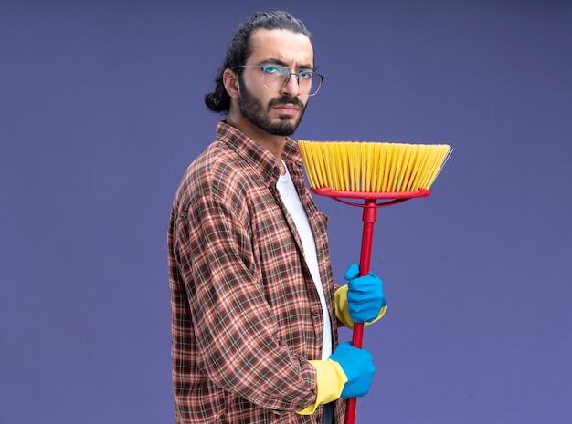 Уверенный молодой красивый парень-уборщик в футболке и перчатках держит швабру, изолированную на синей стене с копией пространства