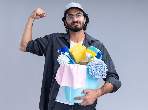 Fiducioso giovane bel ragazzo delle pulizie che indossa t-shirt e berretto che tiene secchio di strumenti di pulizia che mostra forte gesto isolato sulla parete bianca