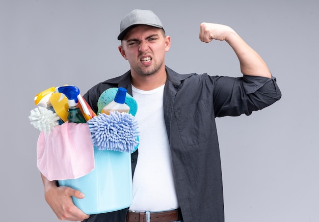Confident young handsome cleaning guy wearing t-shirt and cap holding bucket of cleaning tools showing strong gesture isolated on white wall