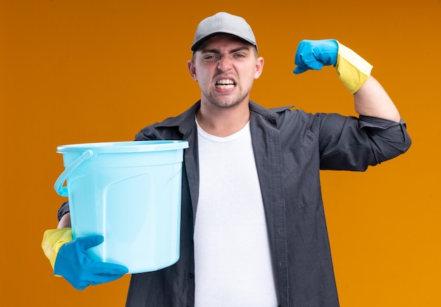 Confident young handsome cleaning guy wearing t-shirt and cap with gloves holding bucket showing strong gesture isolated on orange wall