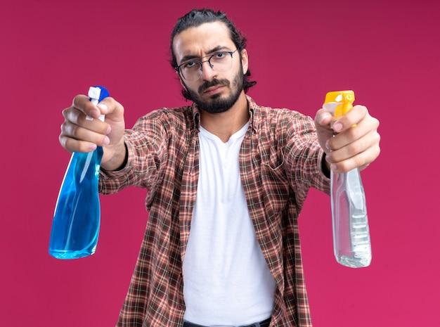 Fiducioso giovane bel ragazzo delle pulizie che indossa una maglietta che tiene fuori le bottiglie spray alla telecamera isolata sul muro rosa