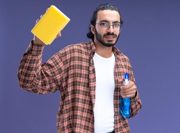 파란색 벽에 고립 된 스폰지와 스프레이 병을 들고 티셔츠를 입고 자신감이 젊은 잘 생긴 청소 남자