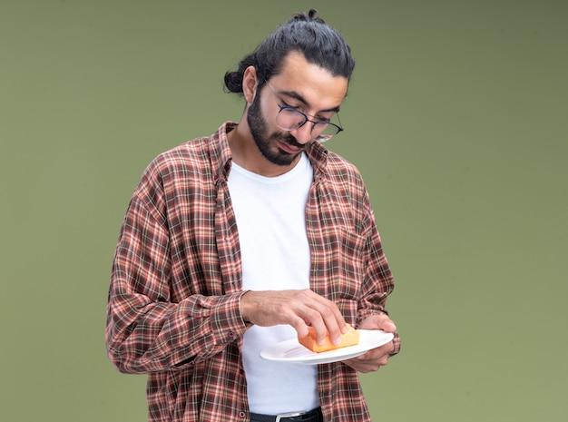 Уверенный молодой красивый уборщик в футболке, мыть посуду с губкой, изолированной на оливково-зеленой стене