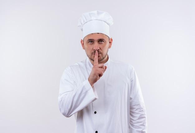 Fiducioso giovane bel cuoco in uniforme da chef che gesturing silenzio isolato sul muro bianco con spazio copia