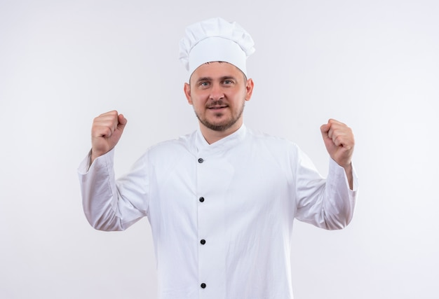 Confident young handsome cook in chef uniform gesturing strong isolated on white wall