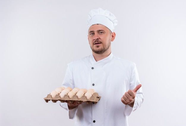 Confident young handsome cook in chef uniform holding carton of eggs and showing thumb up isolated on white wall