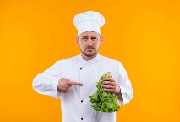 Fiducioso giovane e bello cuoco in uniforme da chef che tiene lattuga e indicandola isolata sulla parete arancione