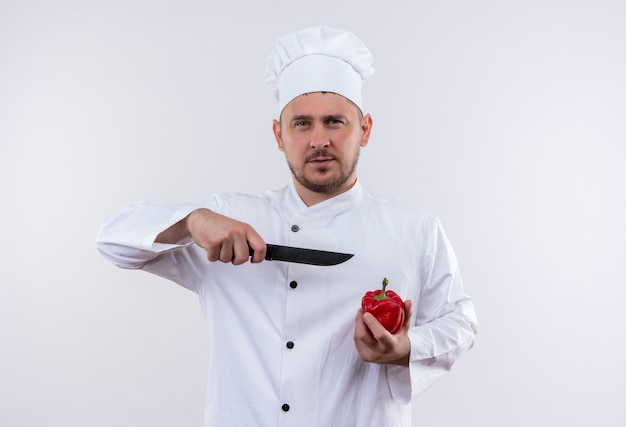 Confident young handsome cook in chef uniform holding pepper and pointing with knife at it isolated on white wall