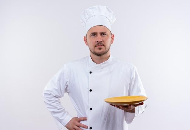 Fiducioso giovane e bello cuoco in uniforme da chef che tiene piatto con un'altra mano sulla vita sul muro bianco isolato