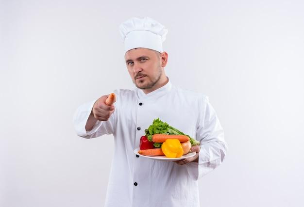 Fiducioso giovane e bello cuoco in uniforme da chef che tiene piatto con verdure e indica con la carota sul muro bianco isolato