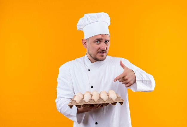 Confident young handsome cook in chef uniform holding and pointing at carton of eggs isolated on orange wall