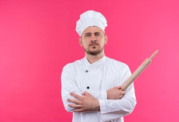 Fiducioso giovane bel cuoco in uniforme da chef che tiene mattarello mettendo la mano sul braccio isolato sul muro rosa pink