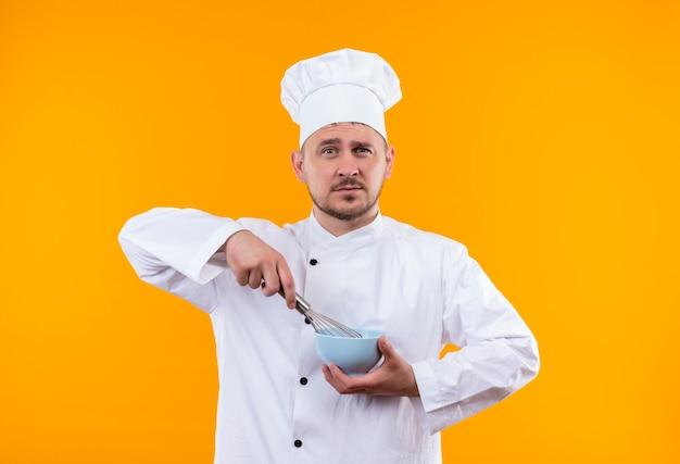 Fiducioso giovane e bello cuoco in uniforme da chef che tiene in mano una frusta e una ciotola isolate sulla parete arancione