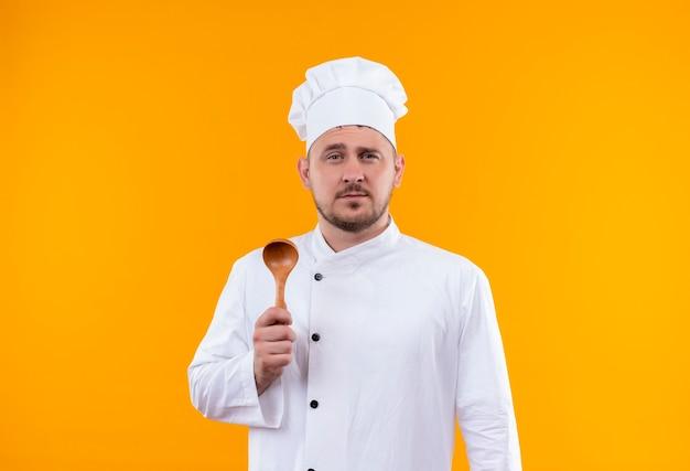 Fiducioso giovane bel cuoco in uniforme da chef con cucchiaio di legno isolato su parete arancione isolated