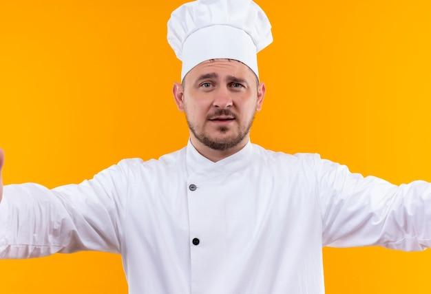 Fiducioso giovane bel cuoco in uniforme da chef sulla parete arancione isolata