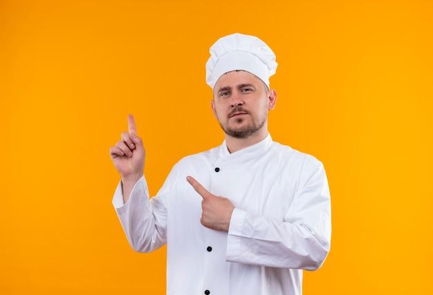 Fiducioso giovane bel cuoco in uniforme da chef rivolto verso l'alto isolato su parete arancione