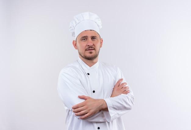 Fiducioso giovane bel cuoco in uniforme da chef in piedi con postura chiusa isolata su muro bianco