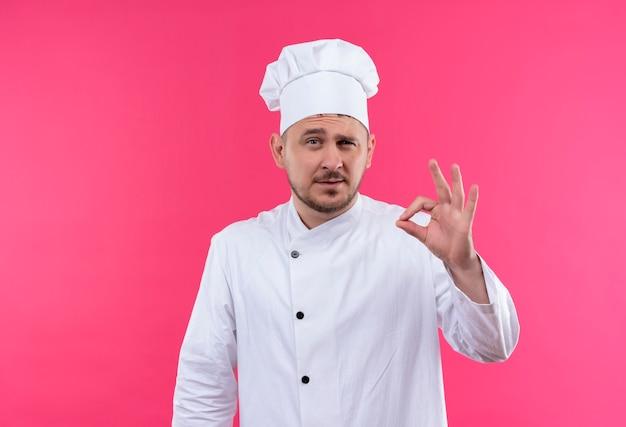Уверенный молодой красивый повар в униформе шеф-повара делает знак ок на розовой стене