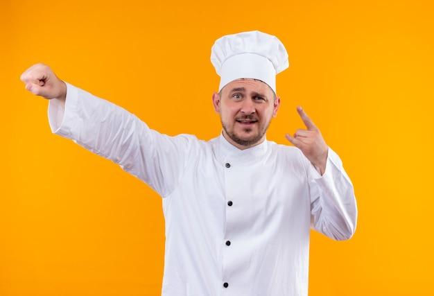 Уверенный молодой красивый повар в униформе шеф-повара делает рок-знак и поднимает кулак на изолированной оранжевой стене