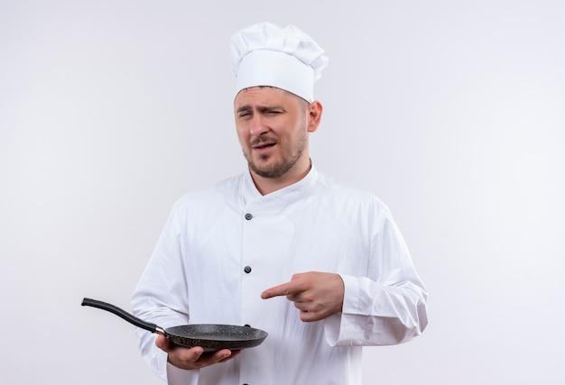 シェフの制服を着た自信のある若いハンサムな料理人が白い壁に分離されたフライパンを押しながら指している