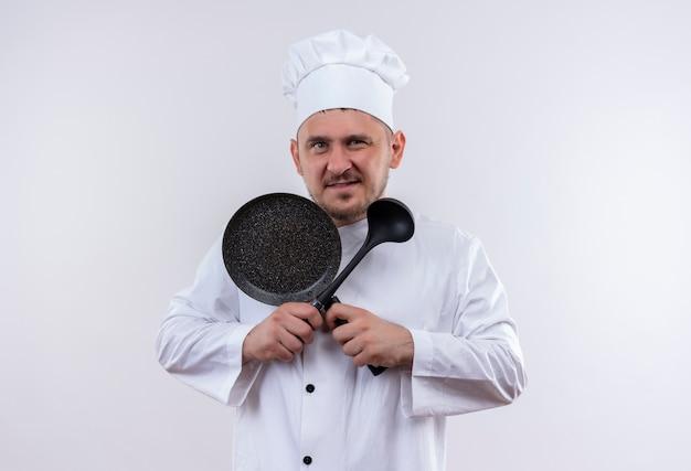 白い壁にフライパンと鍋を保持しているシェフの制服を着た自信のある若いハンサムな料理人