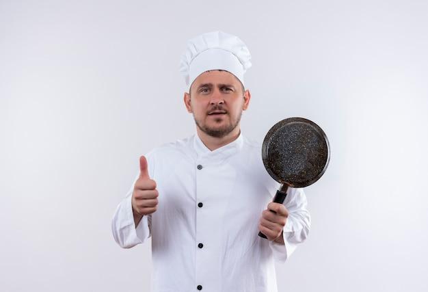 白い壁に孤立した親指を現してフライパンを保持しているシェフの制服を着た自信のある若いハンサムな料理人