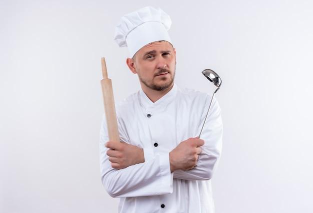 鍋と麺棒を保持しているシェフの制服を着た自信のある若いハンサムな料理人、コピー スペースを持つ孤立した白い壁
