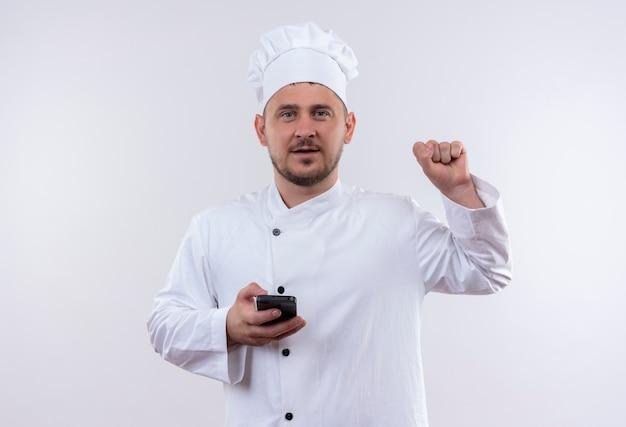 휴대 전화를 들고 흰 벽에 고립 된 주먹을 올리는 요리사 유니폼에 자신감이 젊은 잘 생긴 요리사