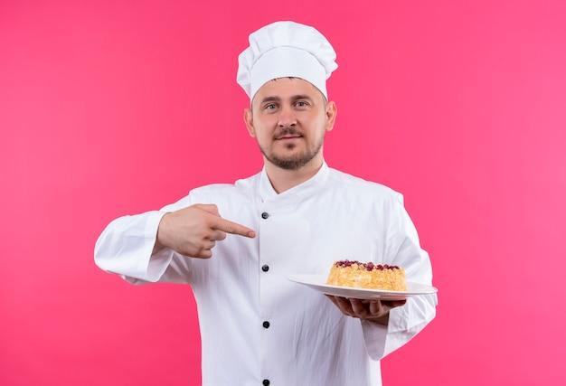 Уверенный молодой красивый повар в униформе шеф-повара держит тарелку торта, указывая на нее, изолированную на розовой стене