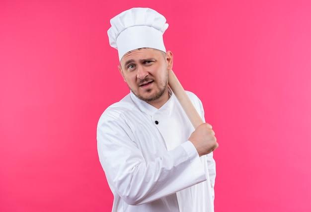 Уверенный молодой красивый повар в униформе шеф-повара держит скалку на розовой стене
